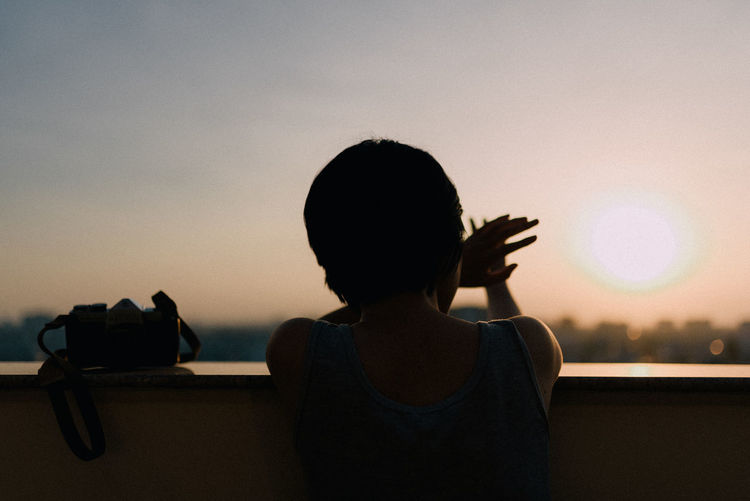 Rear view of woman sitting against sky during sunset