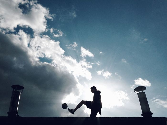 Side view of man paying soccer on building terrace
