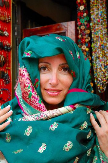 Portrait Of Smiling Young Woman Wearing Scarf At Market