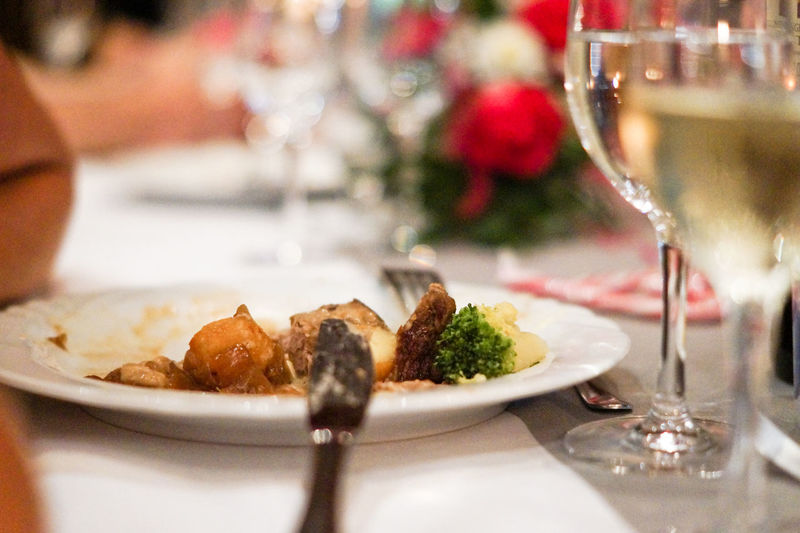 Close-Up Of Meal Served By Wine Glasses On Table