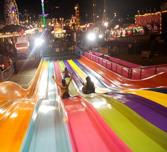 Women Sliding On Illuminated Amusement Park Ride At Night