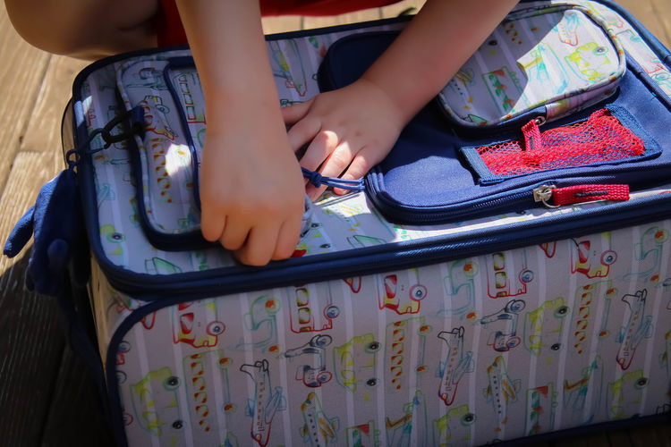 Cropped hands of child holding luggage