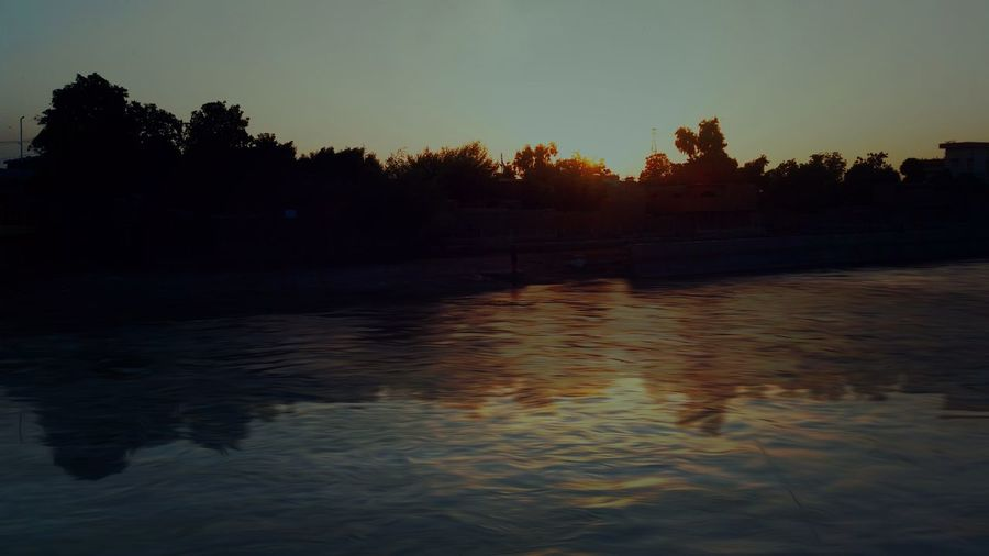 Flows Of Rice Canal Larkana Ali Jawad Photography Photooftheday Lārkāna Sun Orange Sky Sky Sunset Beautiful Moment Ever Love Shine Dark Tree Astronomy Water Tree Area Sunset Forest Lake Beach Reflection Silhouette Shining Seascape Wetland Pine Tree