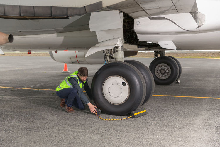 Man working on airplane at airport runway