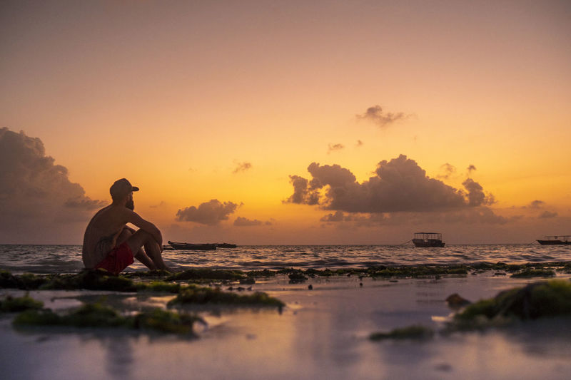 Me watching the sunrise from the beach in Paje Sea Water Sunset Sunrise Outdoors Looking At View Sitting Men Orange Color Sky Beach Ocean Watching View Horizon Over Water Real People Beauty In Nature Morning Zanzibar Boat Calm Chill