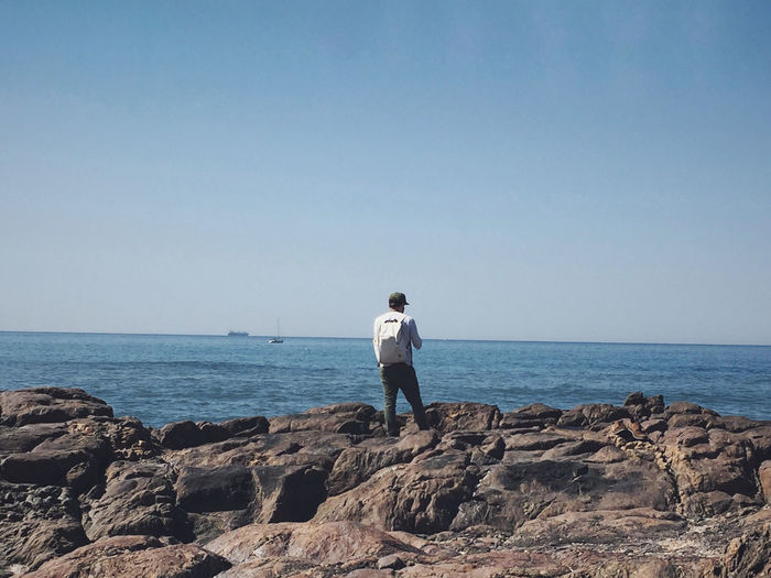 Man standing on rock looking at sea against clear sky