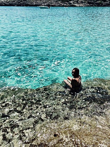 Lagoon Lagoon Water Blue Cristal Clear Blue Sea Water Water Reflections Clear Water Beachphotography Stones Rocky Beach Rocky People Photography People And Places Island Islandlife Island Life Sitting One Person Real People Full Length Lifestyles Nature Young Adult Leisure Activity Outdoors Day Young Women People