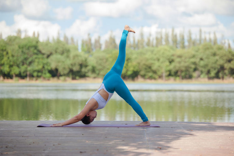 Full Length Of Woman Exercising By Lake