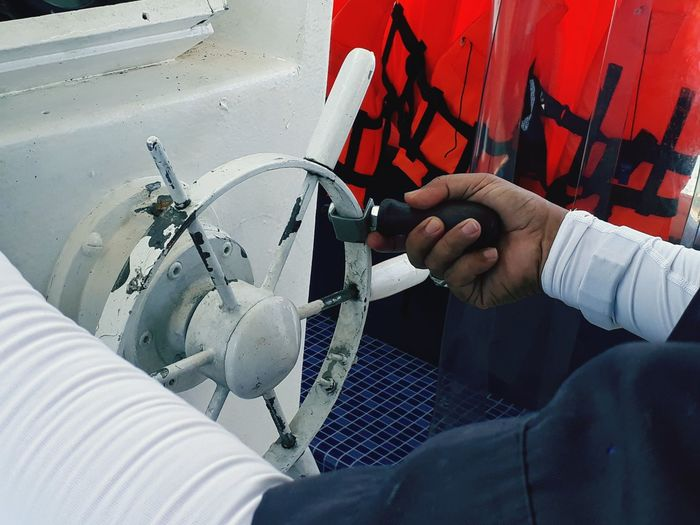 Cropped Hand Holding Steering Wheel In Boat