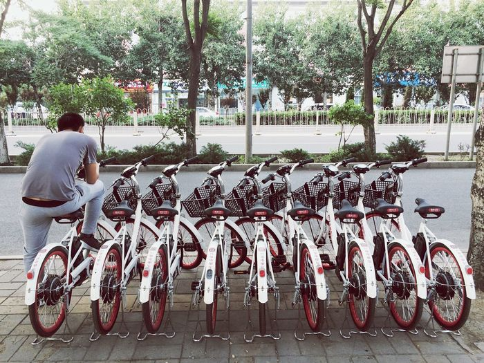 Man Sitting on Bicycle In A Row China's bike-sharing boom in 2017, lines of bikes can now be seen around every corner of streets in major cities. The Street Photographer - 2017 EyeEm Awards