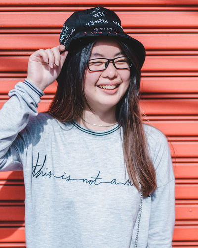 Red Red Background Smiling Happiness Front View One Person Casual Clothing Glasses Real People Portrait Standing Teeth Toothy Smile Emotion Waist Up Lifestyles Leisure Activity Text Eyeglasses  Cap Looking At Camera Hairstyle