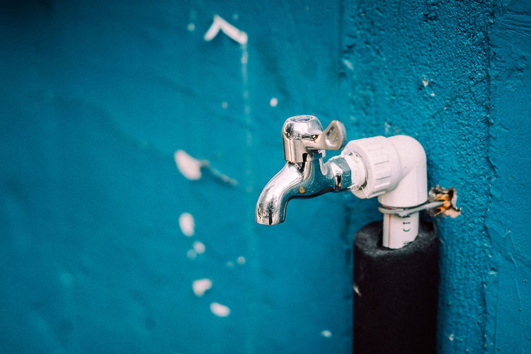 Close-up of tap on blue wall