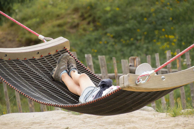 Low section of man relaxing on hammock at playground
