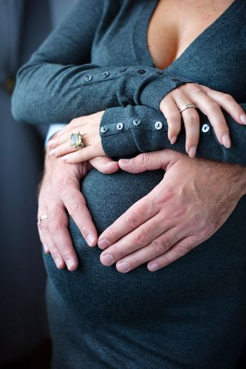 Cropped Hands Of Man Touching Stomach Of Pregnant Woman