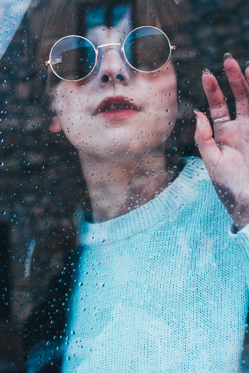 Portrait of woman wearing sunglasses seen though wet window