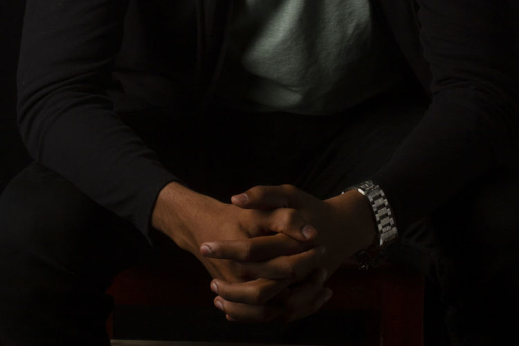 Midsection of man sitting with hands clasped against black background