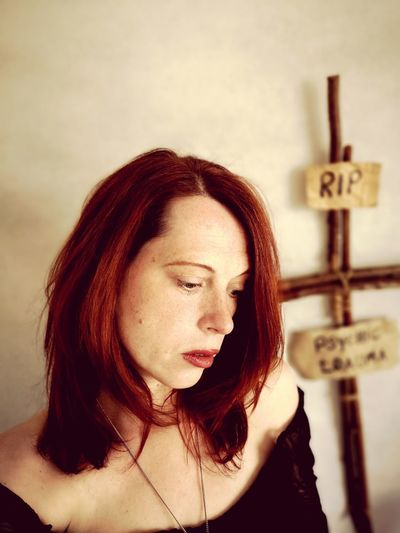 Sad woman standing with cross and text hanging on wall