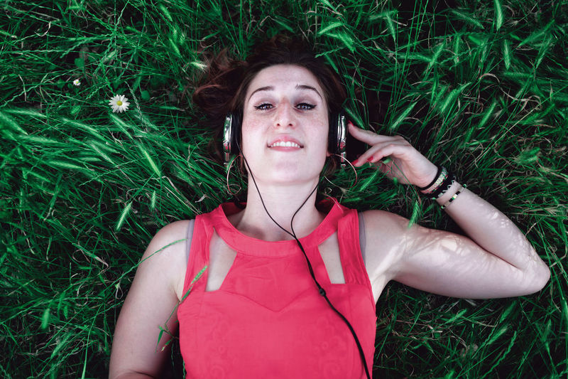 High Angle Portrait Of Young Woman Listening Music While Lying On Grassy Field