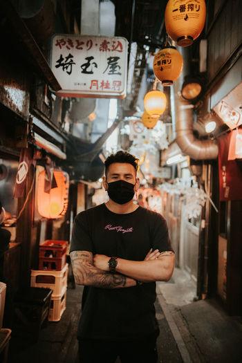 Full length of man standing in illuminated market