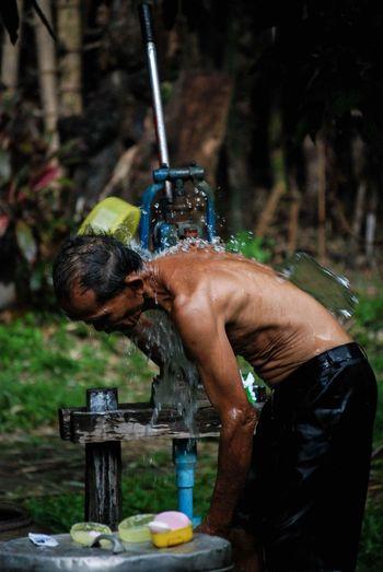 Rear view of shirtless man bathing in water