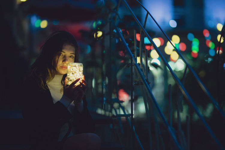 Portrait of young woman holding illuminated lighting equipment while sitting outdoors at night