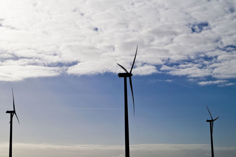 Low angle view of windmills against cloudy sky