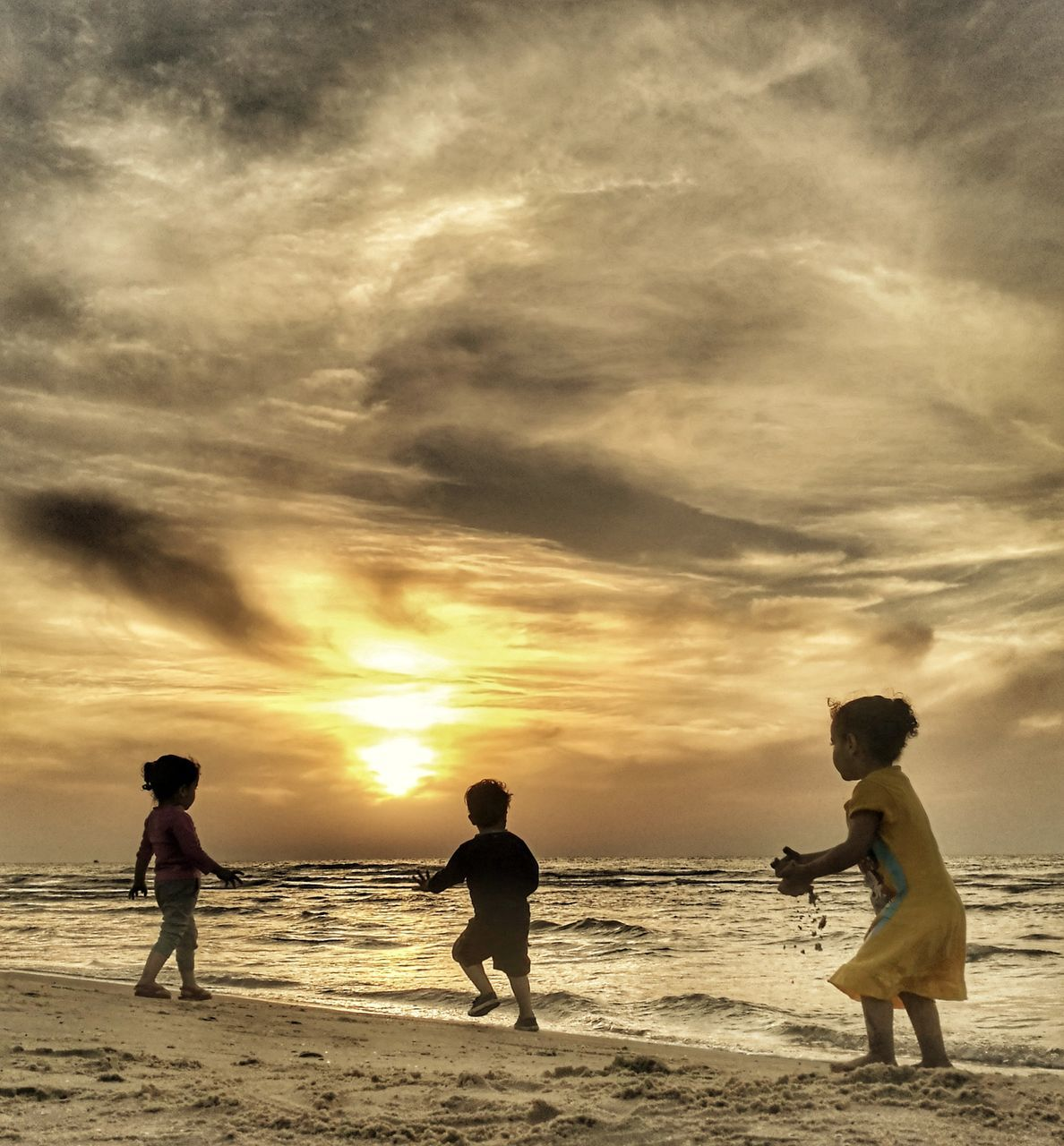 beach, sea, sunset, nature, cloud - sky, shore, sky, beauty in nature, scenics, horizon over water, water, vacations, real people, leisure activity, men, lifestyles, sand, silhouette, outdoors, boys, togetherness, standing, weekend activities, childhood, playing, wave, full length, beach volleyball, day, people