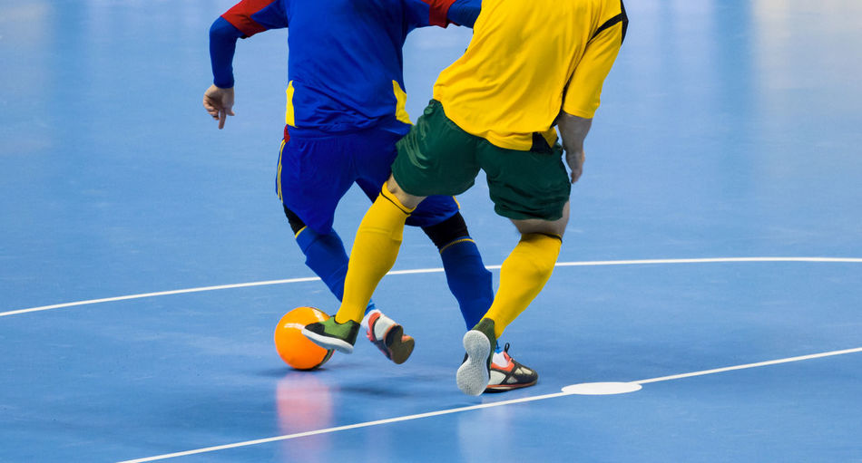Football Futsal Ball and man Team. Indoor Soccer Sports Hall. Activity Athlete Ball Blue Competition Competitive Sport Court Exercising Futsal Futsal Team Healthy Lifestyle Low Section Outdoors People Playing Practicing Running Soccer Soccer Field Soccer Player Sport Sports Clothing Teenager Two People Yellow