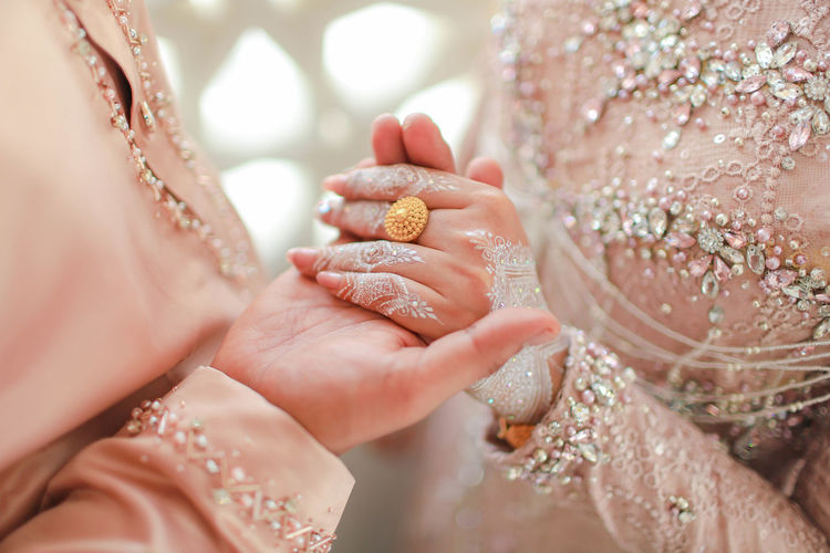Midsection of bridegroom holding hands during wedding ceremony