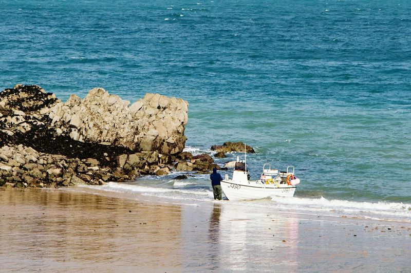 The boat reach the beach at La Greve De Lecq Jersey Jersey Channel Island UK Sea Water Nature Real People Outdoors Beauty In Nature Nautical Vessel Day Men Beach Sky People 3XSPUnity