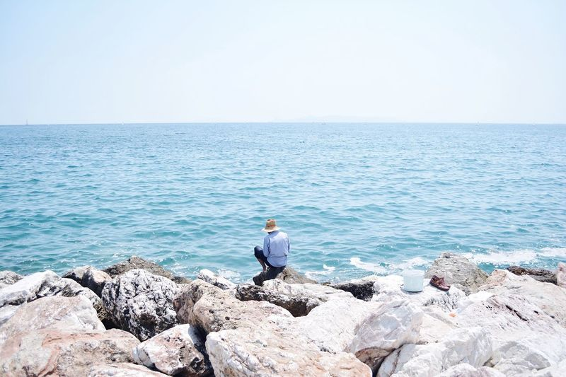 Rear view of man sitting at rocky beach against sky during sunny day