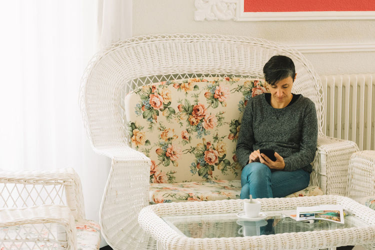 Woman using mobile phone while sitting on chair at home