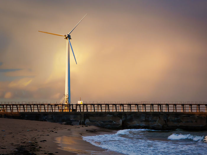 Windmills on sea against sky during sunset