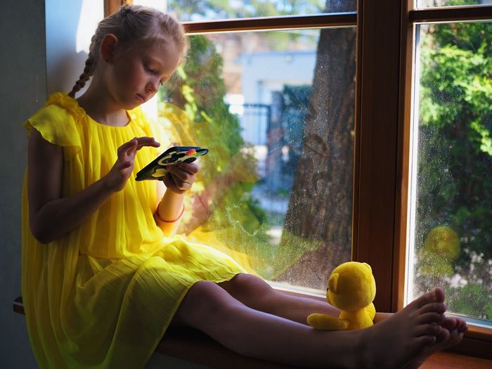 Woman using mobile phone while sitting by window