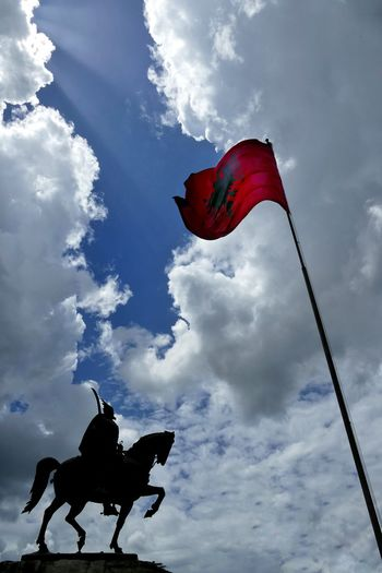 Low angle view of skanderbeg monument with albanian flag against sky