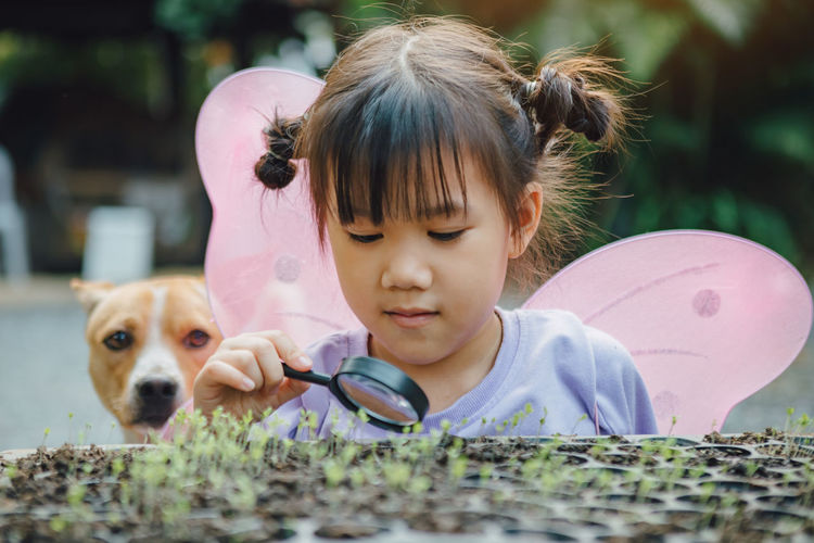 Cute girl holding magnifying glass by plants with dog in background