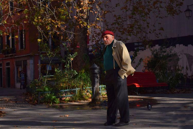 Senior man standing by tree on street
