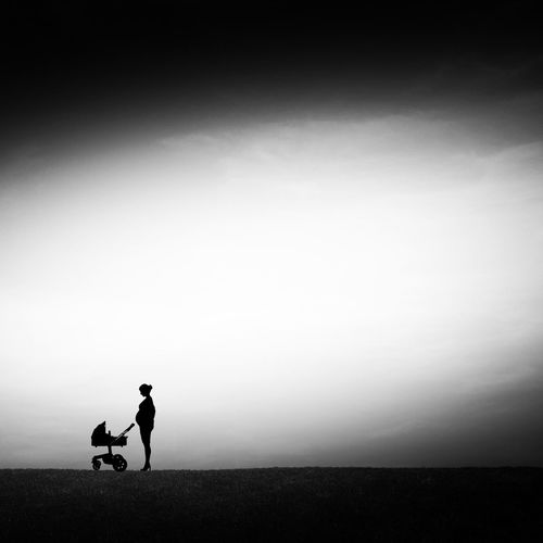 Silhouette Of Woman With Baby Carriage