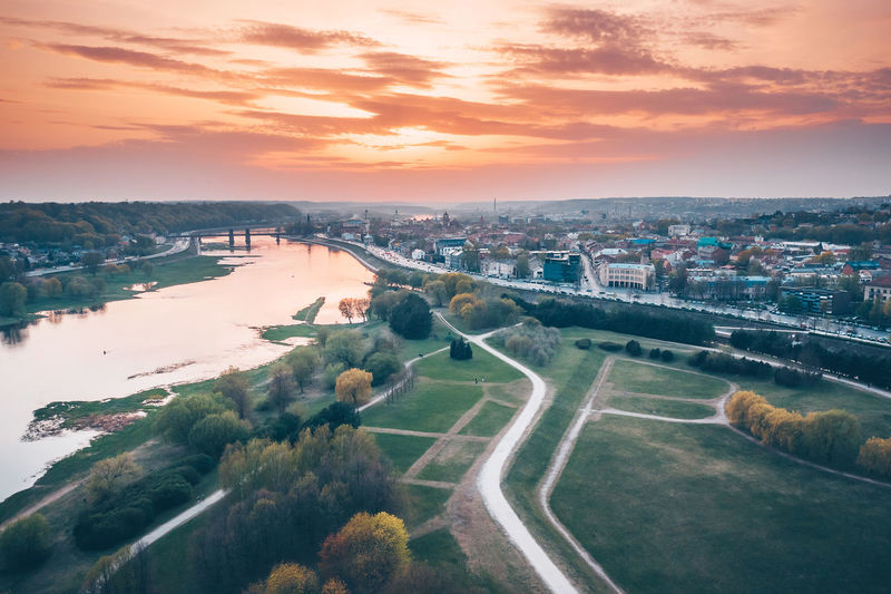 High angle view of townscape by river against sky during sunset