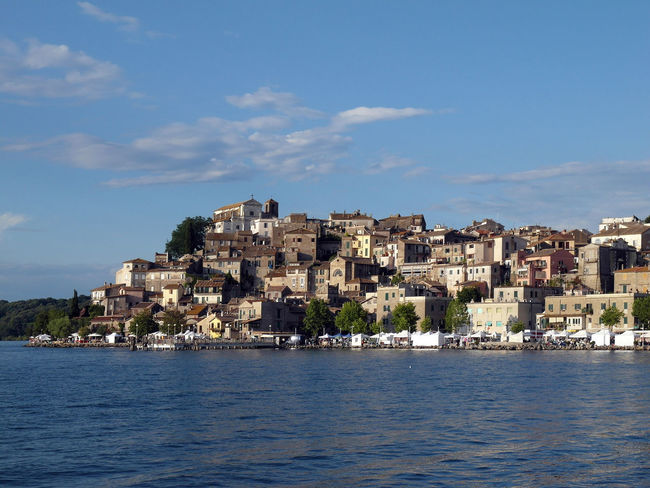View Anguillara Anguillara Sabazia Architecture Blue Blue Sky And Clouds Building Exterior Built Structure City Cityscape Clouds Clouds And Sky House Lago Di Bracciano Lake Lazio Nature Outdoors Residential Building Ripple Rippled Water Sky Town Travel Destination View Into Land Water Waterfront
