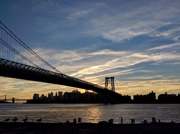 Suspension bridge over river at dusk