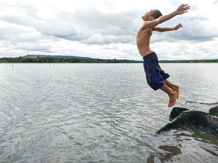 Full length of shirtless man jumping in lake against sky