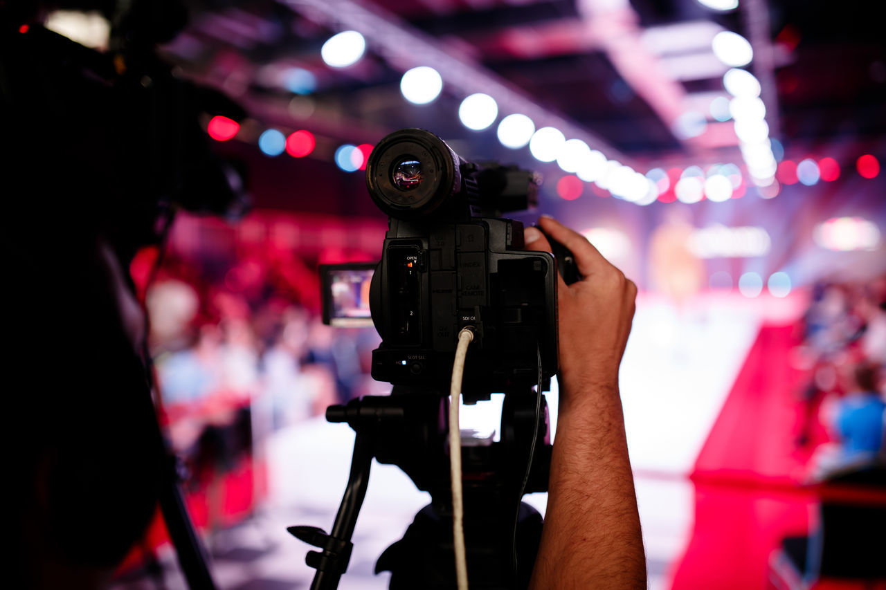 Cropped hand of photographer adjusting television camera on tripod at fashion show