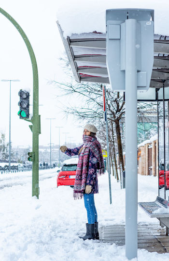 Rear view of woman with umbrella on snow covered street