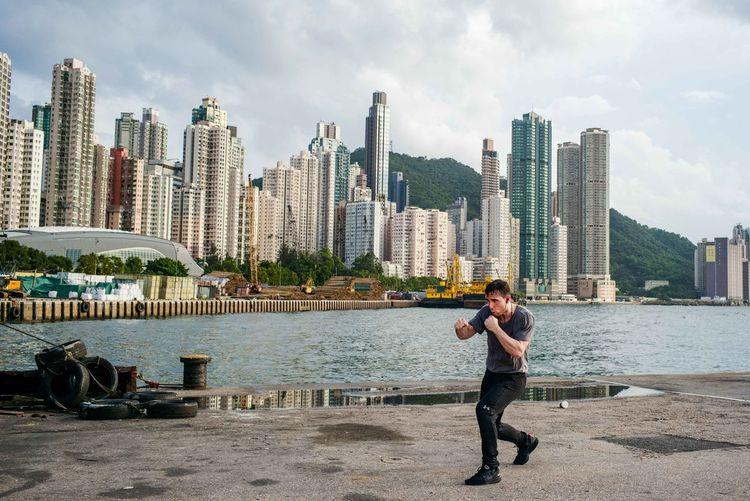 Full length of man standing by modern buildings in city against sky