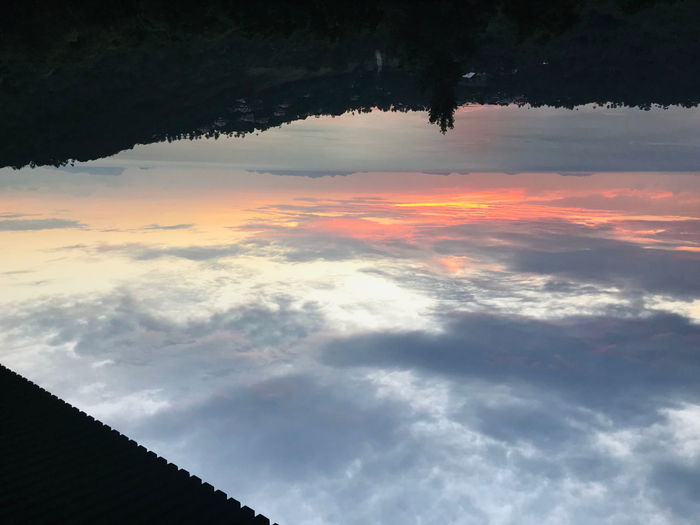 Low angle view of silhouette roof against sky during sunset
