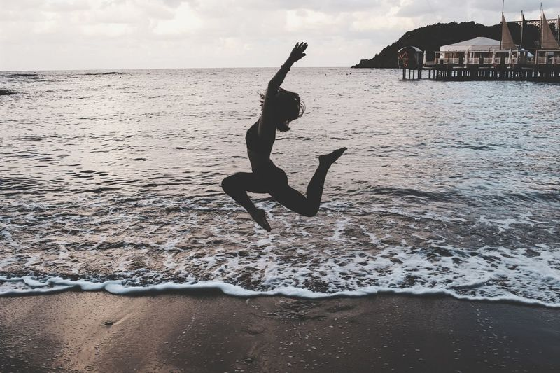 Full length of woman jumping over sea against sky