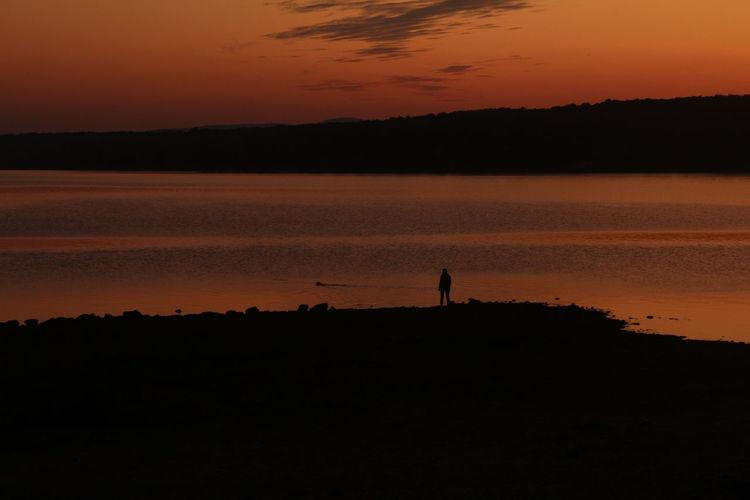 Silhouette man standing by lake against orange sky