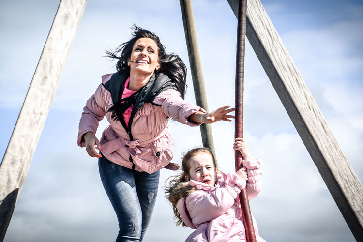 Mother pushing daughter sitting on swing in playground against sky