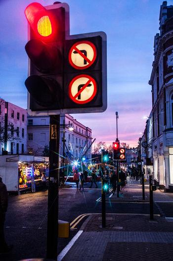 Illuminated road sign on city street at night